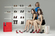 three young women sitting trying shoes looking happy