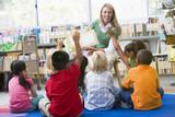 Kindergarten teacher reading to children in library