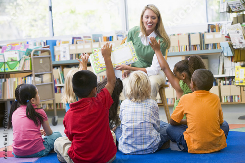 Kindergarten teacher reading to children in library - 31993783