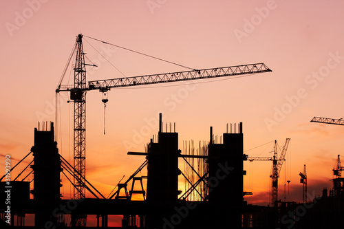 construction site with construction cranes at sunset