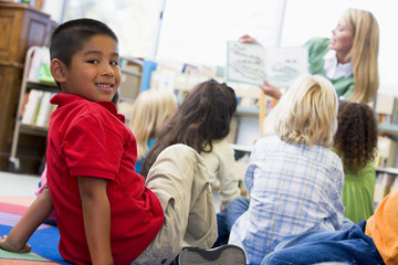 Kindergarten teacher reading to children in library, boy looking