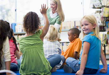 Kindergarten teacher reading to children in library, girl lookin