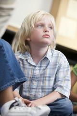 Boy daydreaming at kindergarten