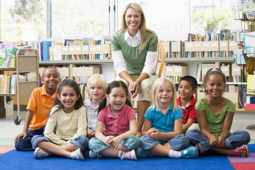 Kindergarten teacher sitting with children in library