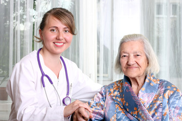 Smiling doctor takes care an elderly women