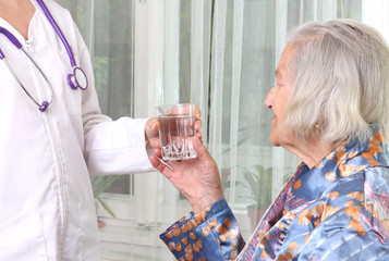 Doctor gives a glass of water to the patient