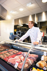 Cheerful chef on the counter of frozen meat