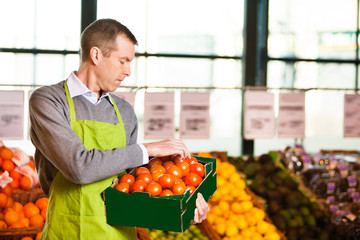 Market assistant holding box of tomatoes