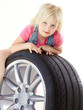 Cute blond girl playing with a summer tyre