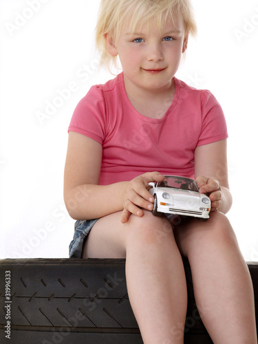 Blond girl sitting on a tyre and playing with a toy car