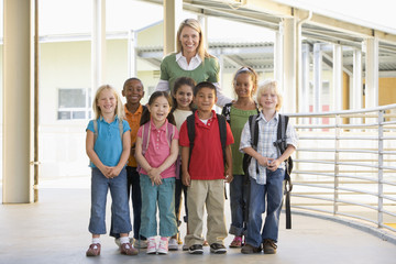 Kindergarten teacher standing with children in corridor