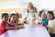 Kindergarten teacher supervising children eating lunch