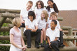 School children sitting on benches outside with their teacher