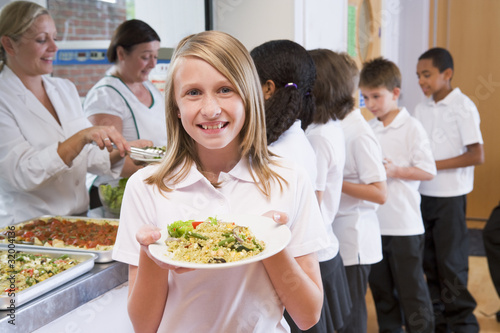 Schoolgirl holding plate of lunch in school cafeteria - 32004136