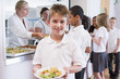 Schoolboy holding plate of lunch in school cafeteria - 32004700