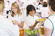 Lunchladies serving plates of lunch in school cafeteria
