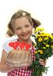 Mädchen hält einen Kuchen und Blumen