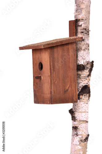 Real estate concept - wooden birdhouse on birch stem isolated