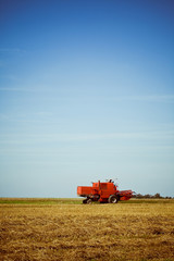 Red combine harvester working in a wheat field