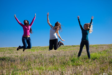 three young beautiful woman jumping into the field against the s