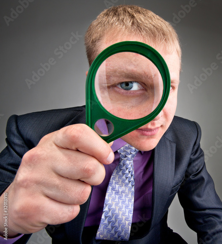 Worried businessman looking through magnifier lens