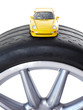 Yellow toy car on top of a low section tyre