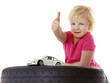 Little cute girl sitting on a tyre with toy car shows thumb up