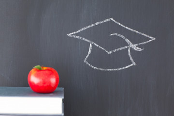 Stack of books with a red apple and a blackboard with a graduati