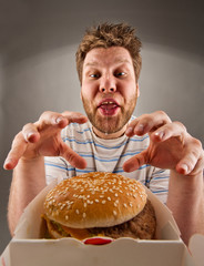 Happy man preparing to eat burger