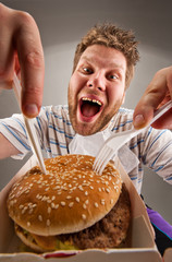 Man with knife and fork eating burger