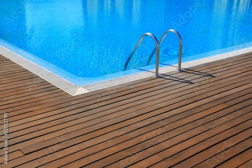 blue swimming pool with teak wood flooring
