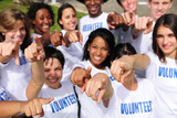 happy volunteer group pointing towards camera
