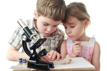 Curious little boy and girl draw diagram near microscope