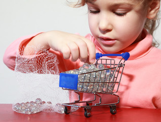 Cute little girl care play with toy shopping trolley