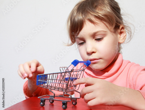 Cute little blond girl care play with empty toy shopping trolley