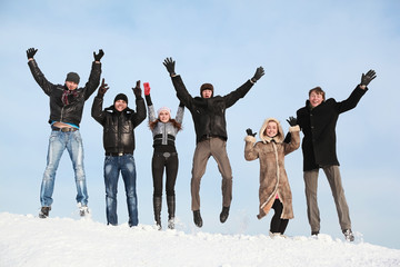Students jump in winter on to snow and lift hands upwards