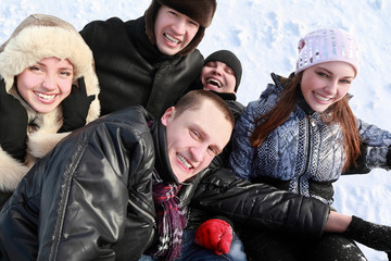 Young people by winter day lie on snow in heap and laugh