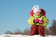 little girl in green jacket sitting at snow outdoors at winter