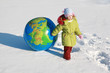 little pensive girl drags big inflatable globe on outdoor