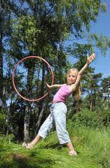 Little girl having fun with hula hoop