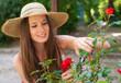 jolie jeune femme qui s'occupe des rosiers