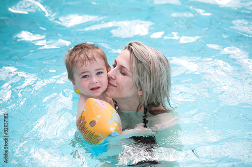 Young mother and child in blue pool