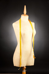tailor mannequin with tape measure on black background