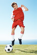 Excited small soccer player jumping in joy