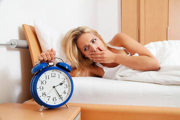 Schlaflos mit Uhr in der Nacht.
