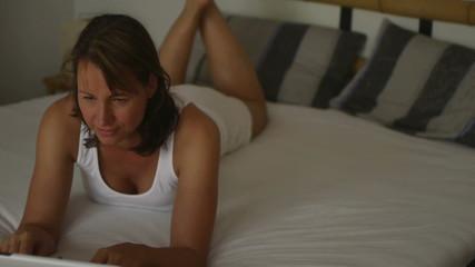 Frau im Bed arbeitet am Computer