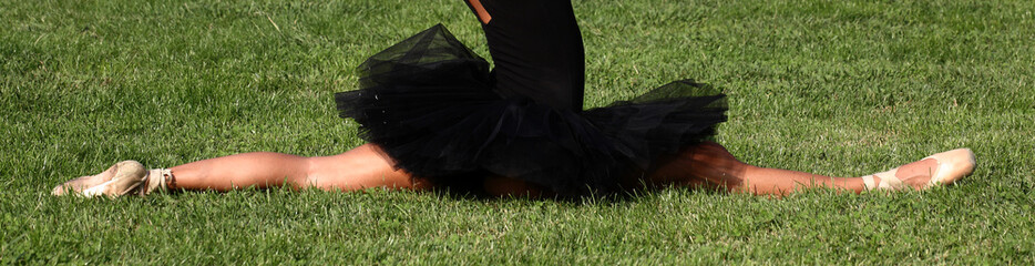 ballrina con tutù nero in spaccata sul prato