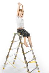 Kid sitting on top of stepladder, hands raise up.