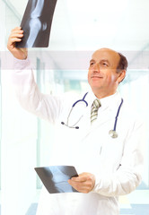 successful caucasian man doctor examining x-ray photos.