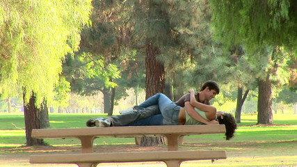 Young couple being affectionate on a park bench